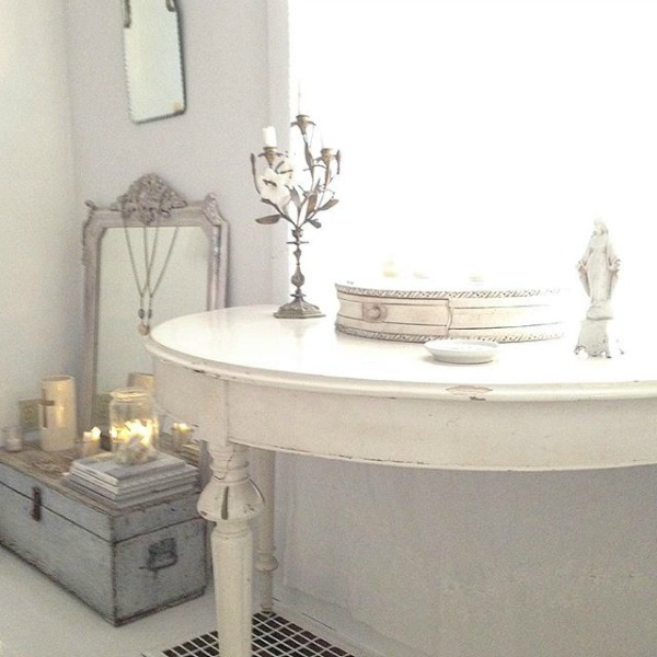An all white interior with Nordic French style has a demilune table and vintage accents - My Petite Maison. Visit this story for even more gorgeous photos of rooms with a tone on tone quiet elegance.
