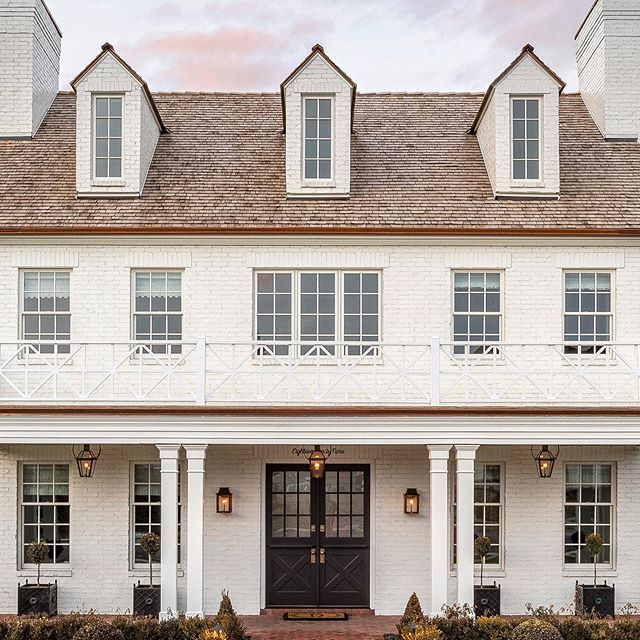 Breathtaking traditional white home exterior of new build by The Fox Group with dormers and double door entry.