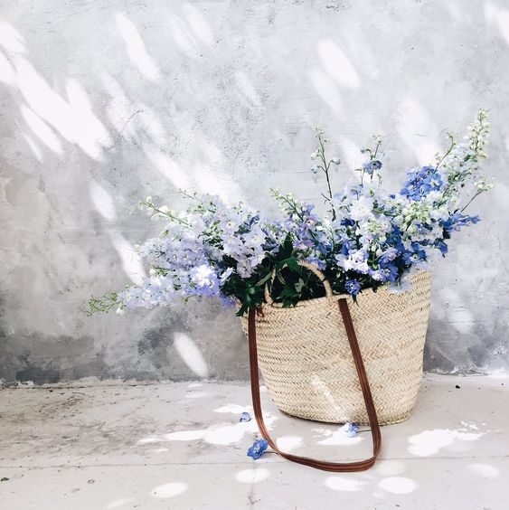 French market basket from Vivi et Margot filled with blue flowers.
