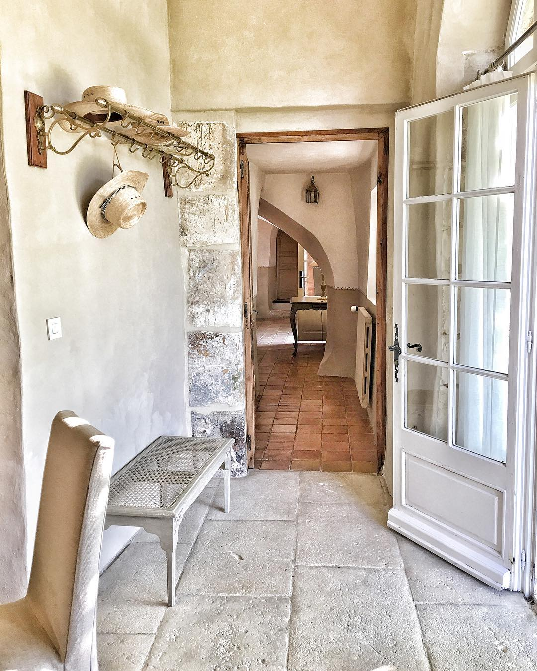 French farmhouse in France entry with coat rack and charming rustic decor. Photo by Vivi et Margot.