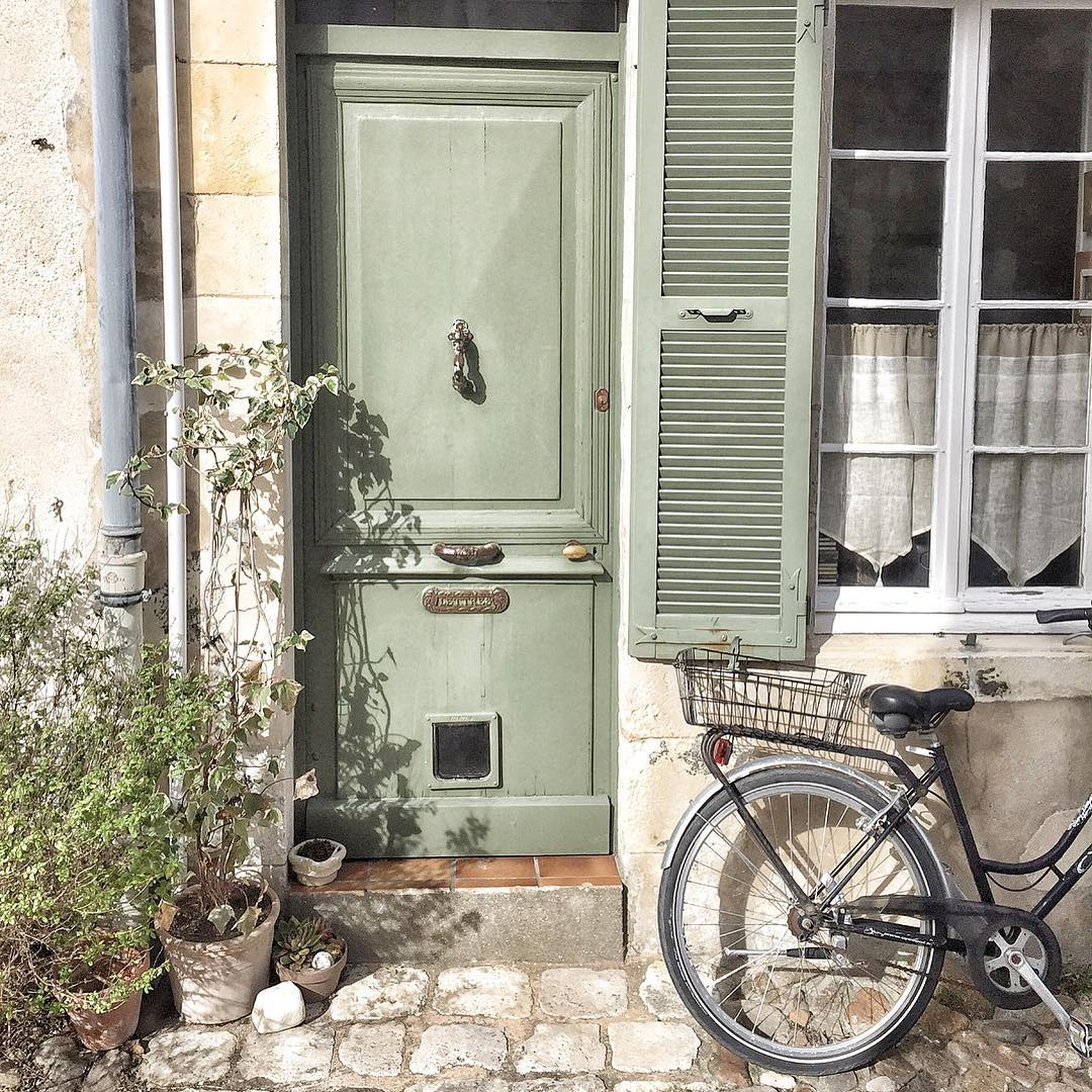 Charming and rustic French farmhouse front door, vintage bicycle, and exterior with Vert Olivier Green Shutters - photo by Vivi et Margot.
