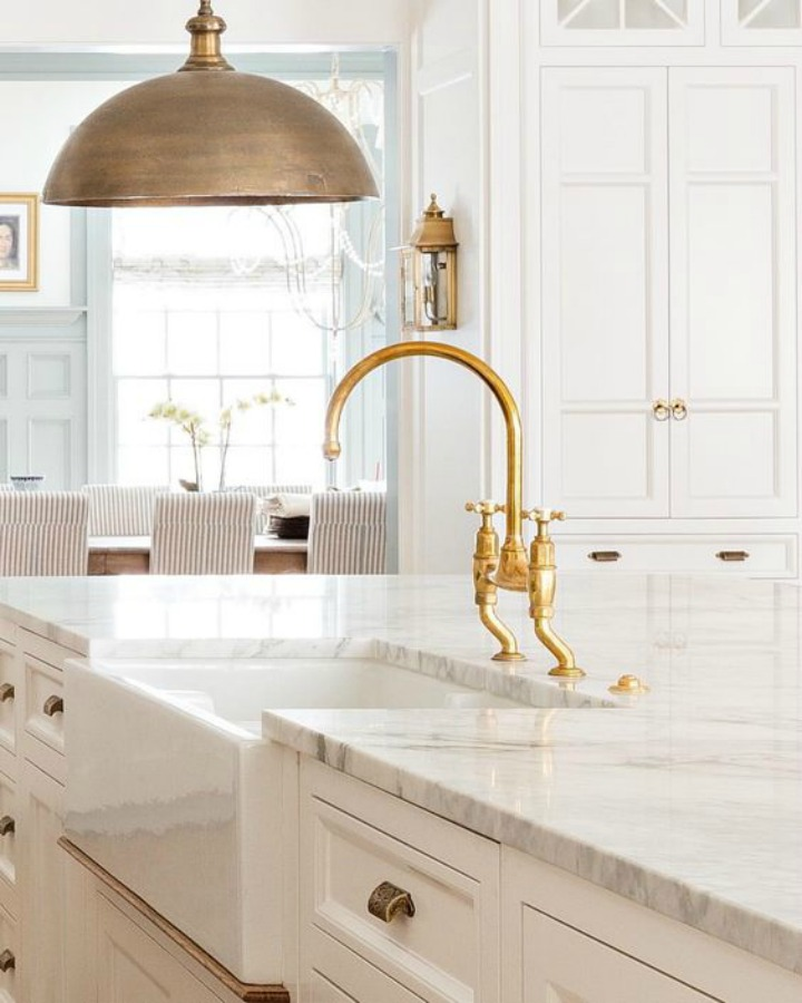 Beautiful white timeless kitchen with marble countertop, brass kitchen faucet, and dome pendant - design by The Fox Group.  Click through for 9 Tranquil, Traditional, Timeless Interior Design Ideas & Inspiring House Exteriors: The Fox Group!