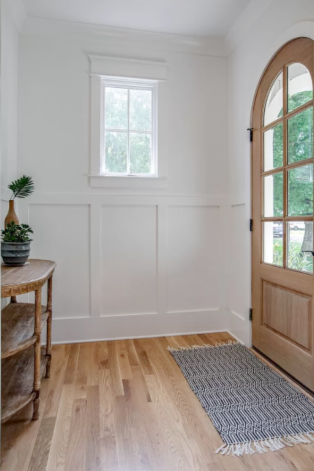Arched wood front door and board an batten wall in entry of a charming Franklin, TN cottage. #entry #interiordesign