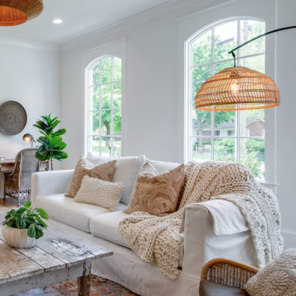 Comfy white sofa with gold pillows, cableknit chunky throw, and rattan lighting accents in a rustic cottage den in Tennessee.