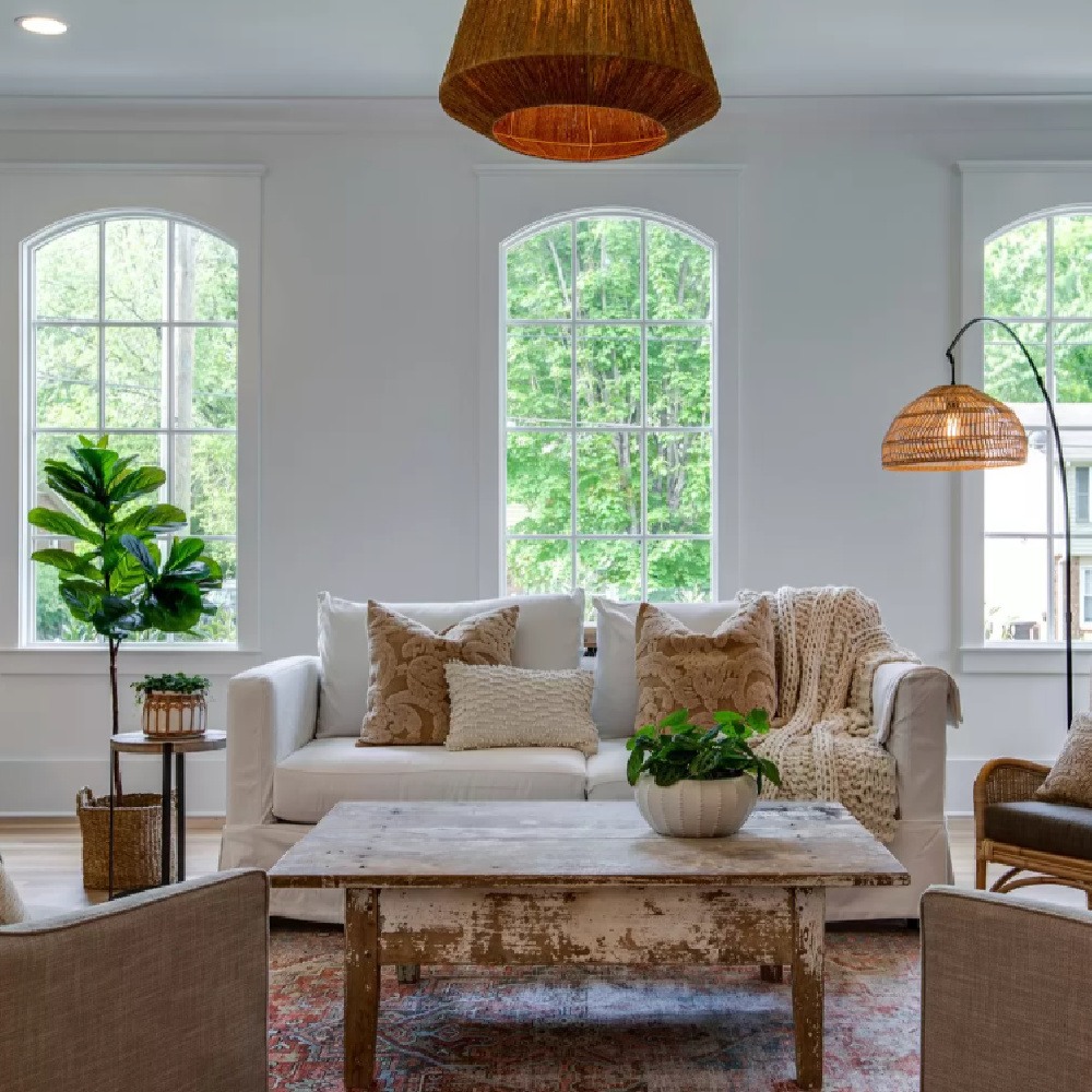 Wicker pendant and white sofa in a netural Southern cottage den with rustic fireplace and raw wood coffee table.