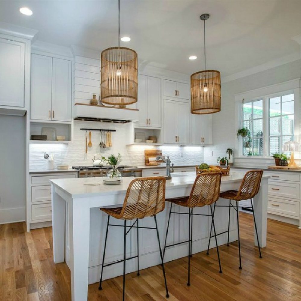 Breezy white Shaker kitchen with natural organic woven pendants and counter stools in a Tennessee cottage. #beachykitchen #shakerkitchen