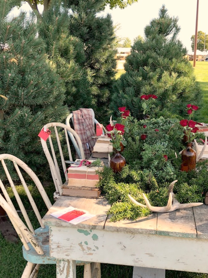 Vintage holiday tablescape outdoors with evergreen trees! Autumn inspiration, Fall farmhouse style decor, vintage wares, and handmade treasures mingle at Main Street Market (Urban Farmgirl) in Belvidere, Illinois - Hello Lovely Studio. #fleamarket #farmhousestyle #vintage #junkin
