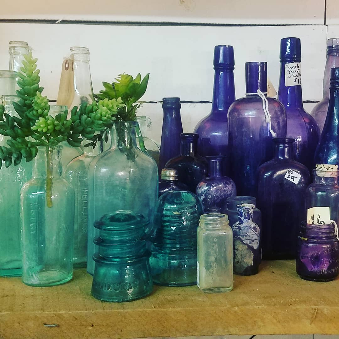 A collection of antique colorful bottles at Scarlett Scales Antiques. CLICK OVER to my place to discover 4 Charming Franklin Tennessee Shops for Vintage, Antiques & Farmhouse Decor Finds!