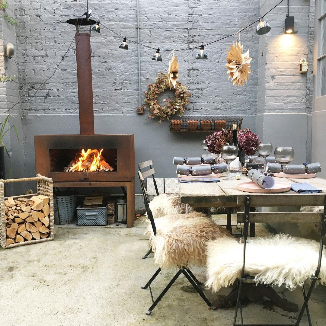 English country courtyard with fireplace and dining chairs covered with sheepskins - Imperfect Interiors. #englishcountry #courtyard #outdoordining #wintercourtyard