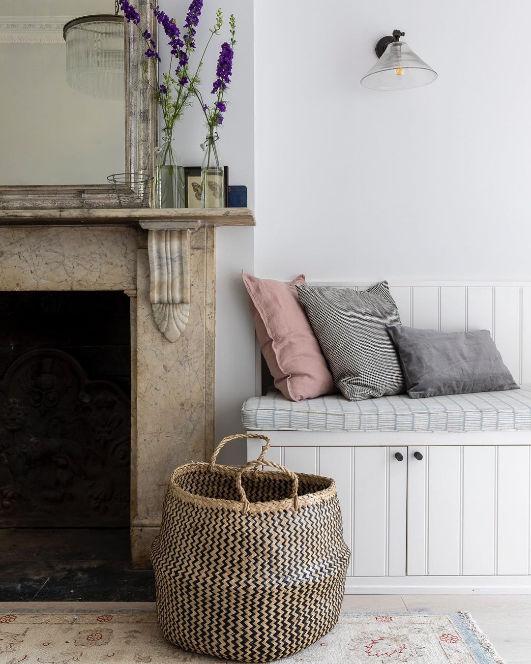 Detail of an antique marble fireplace, antique rug, and built-in bench in a beautifully designed space by Imperfect Interiors. #fireplace #antiques #interiordesign #serenedecor #englishcountry