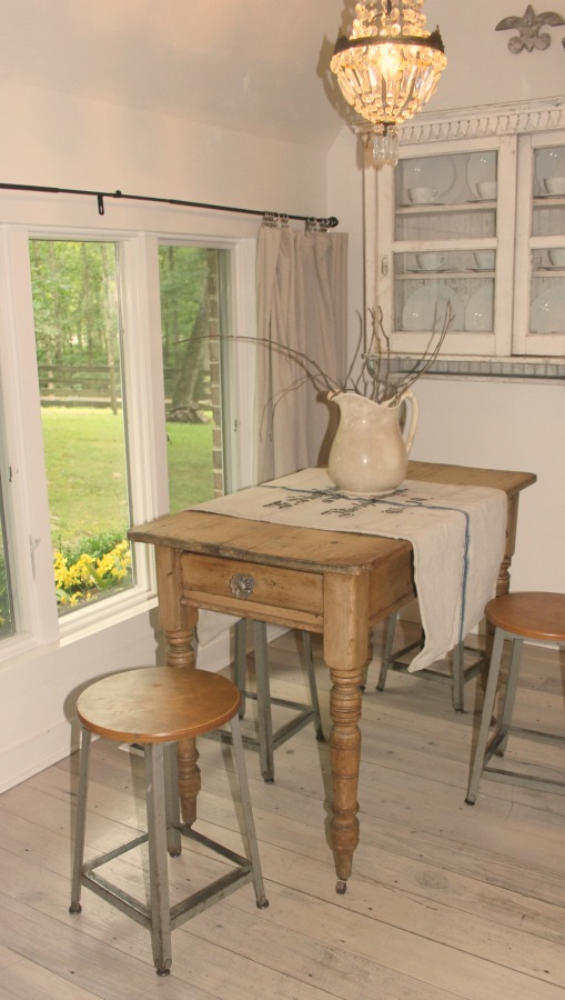 Vintage farmhouse table with turned wood legs and stools is adorned with a vintage German grainsack and ironstone pitcher at Storybook Cottage in Leiper's Fork, TN.