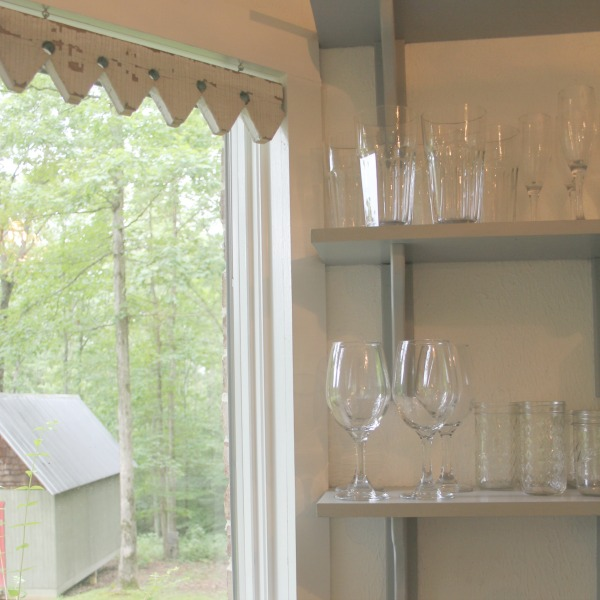 Detail of unique salvaged architectural window treatment. From the blue grey cabinet doors with cross cut out detail to the open shelving, this farmhouse kitchen designed by City Farmhouse for Storybook Cottage in Leiper's Fork, TN, sings with vintage country style! Photo by Hello Lovely Studio. #farmhousekitchen #cityfarmhouse #storybookcottage