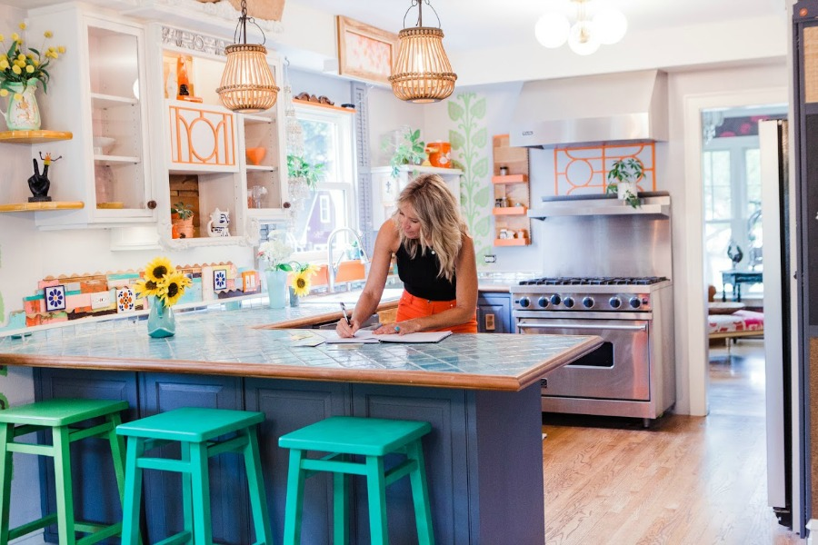 Be inspired by this photo gallery of vibrant colorful beachy boho interior design from artist Jenny Sweeney's Chicagoland home. Her art has been lifting spirits and opening hearts to wonder - see how it lives large in a charming suburban Tudor! #bohemian #interiordesign #colorful