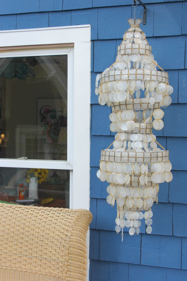 Capiz shell pendant against bold blue cedar shake siding of a cottage by Jenny Sweeney.