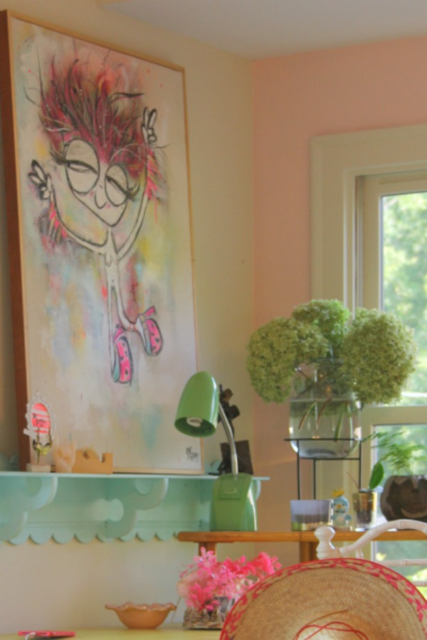 Candy pink painted walls, whimsical art, and colorful vintage treasures mix in an office nook by Jenny Sweeney. #desk #colorfuldecor #vintagestyle #pinkwalls
