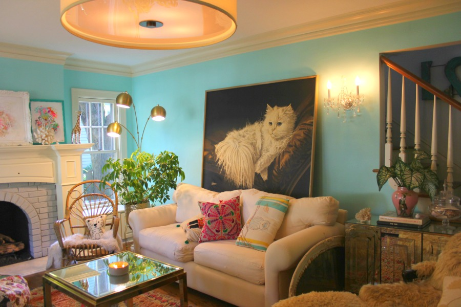 An enormous vintage painting with a fluffy white cat against a bright turquoise painted wall in a colorful boho living room by Jenny Sweeney. #vintagestyle #colorful #interiordesign #boho #whitecat