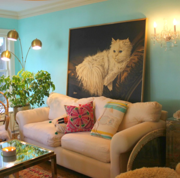 An enormous vintage painting with a fluffy white cat against a bright turquoise painted wall in a colorful boho living room by Jenny Sweeney. Time to Paint Your Walls? Come discover a Refresher to Demystify the Process!