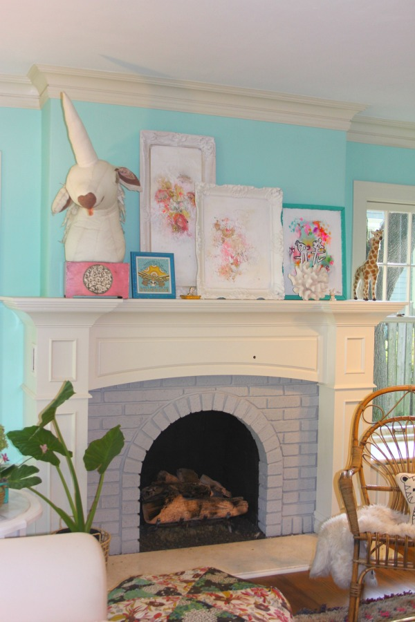 Whimsical art by Jenny Sweeney lines the fireplace mantel in a quirky Libertyville, IL cottage.
