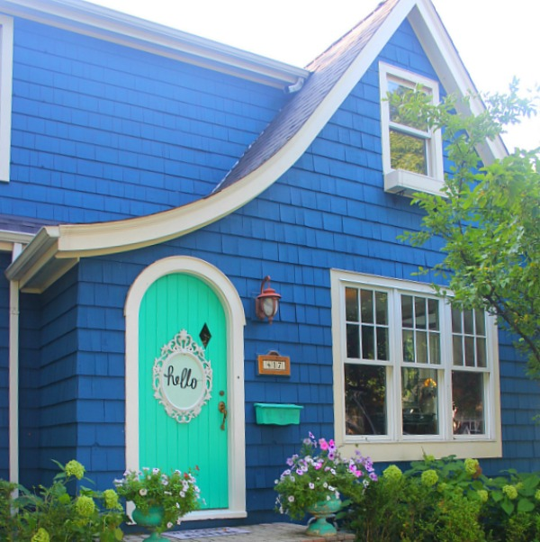 Bold blue painted Tudor cottage with arched door and whimsical front porch decor - Jenny Sweeney! #cottage #exterior #colorful #royalblue #colorfulhome #archdoor