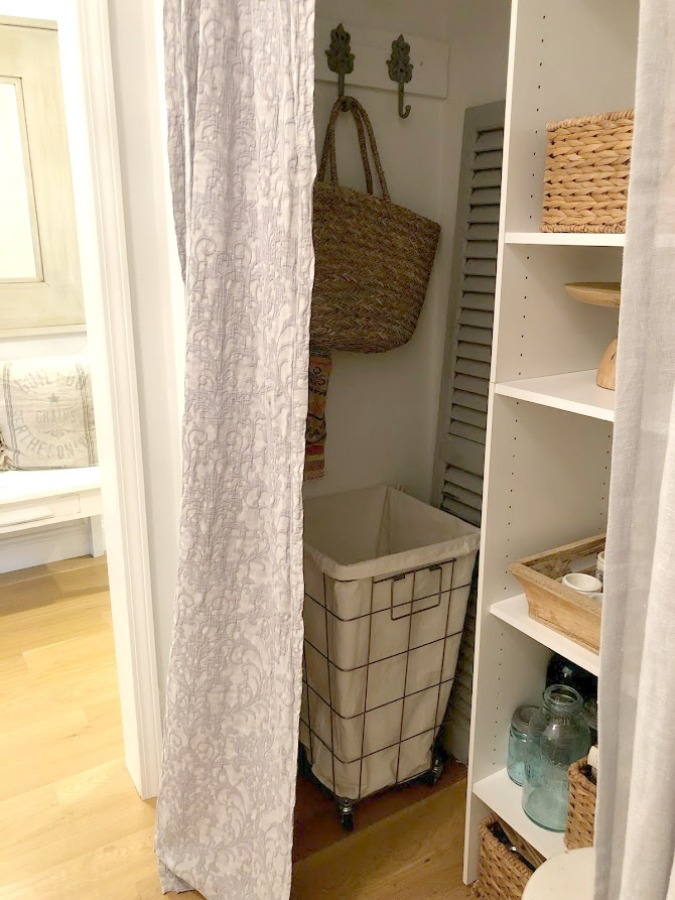Come see how I made our awful little pass through laundry room next to the garage function better and look peaceful with simple inexpensive DIY - Hello Lovely Studio. #beforeafter #laundryroom #diy #makeover #serenedecor