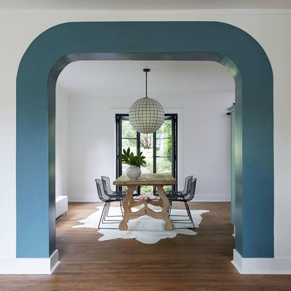 Blue Blood PPG paint color is used as a unique stripe around an archway in a dining room on HGTV;s Restored by the Fords with design by Leanne Ford. #blueblood #ppg #paintcolors #interiordesign #leanneford #restoredbythefords #diningroom #stripe