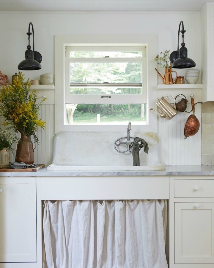 Rustic and vintage style are mellowed with white paint, a soft skirt at the sink, and edgy barn style sconces flanking the window. Design by Leanne Ford and photo by Reid Rolls for HGTV Restored by the Fords. #rustickitchen #vintagestyle #leanneford #restoredbythefords