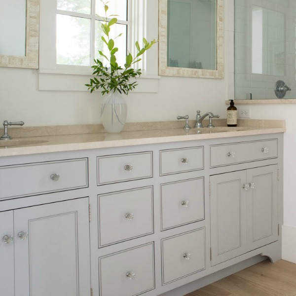 This bathroom vanity in a coastal cottage is painted Tinsmith by Sherwin Williams. Designed by Lisa Furey.Click through for Perfect Light Gray Paint Colors You'll Love as Well as Interior Design Inspiration Photos. #bestgreypaint #paintcolors