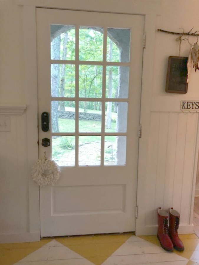 Farmhouse charm and vintage style in a charming entry with white paneling and bold yellow painted poplar floors greeting you at Storybook Cottage in Leiper's Fork near Franklin, TN. The interiors designed by Kim Leggett of City Farmhouse inspire! #farmhousedecor #storybookcottage #entry