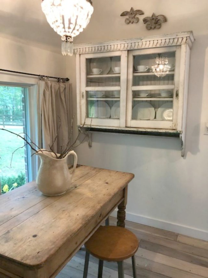 From the blue grey cabinet doors with cross cut out detail to the open shelving, this farmhouse kitchen designed by City Farmhouse for Storybook Cottage in Leiper's Fork, TN, sings with vintage country style! Photo by Hello Lovely Studio. #farmhousekitchen #cityfarmhouse #storybookcottage