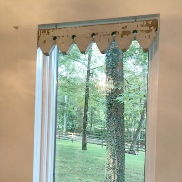Detail of architectural salvage trim used as window treatment in farmhouse kitchen at Storybook Cottage.