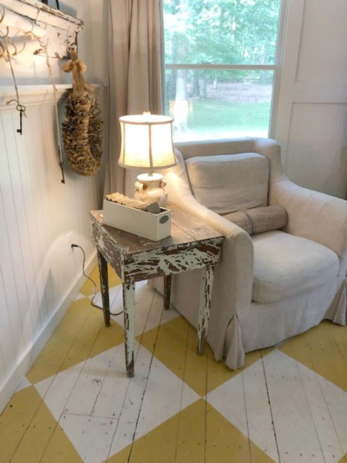 Farmhouse chic living room with vintage treasures, bold yellow painted poplar wood flooring, linen upholstery, and design by City Farmhouse for Storybook Cottage in Leiper's Fork, TN - Hello Lovely Studio. #farmhousestyle #livingroom #cityfarmhouse #storybookcottage