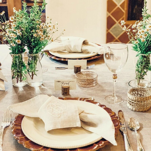 A rustic yet elegant Cali organic tablescape with woven textures and charming knotted cloth napkins at each placestting - After Orange County. #clothnapkins #tablescape #entertaining #organic #rusticelegance