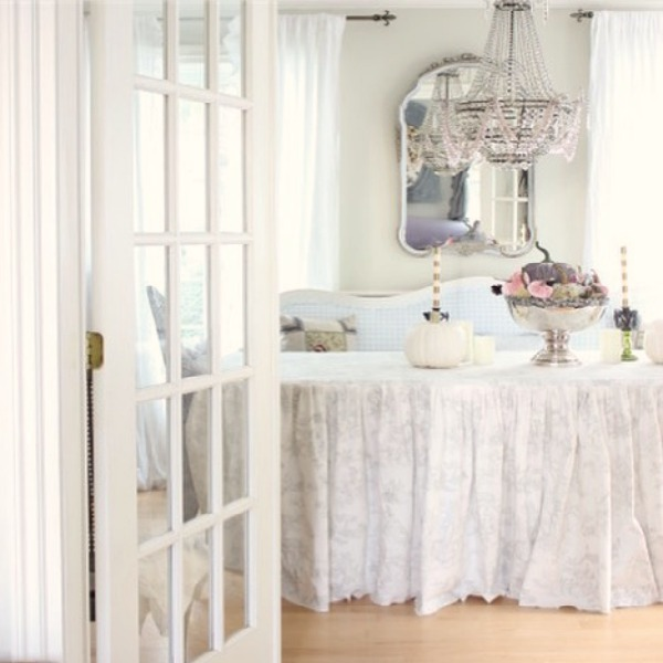 Romantic French charm abounds in a dining room with a custom toile skirted table and Empire style crystal chandelier - Maison Decor. #frenchcountry #diningroom #interiordesign #skirtedtable #romanticdecor #cyrstalchandelier
