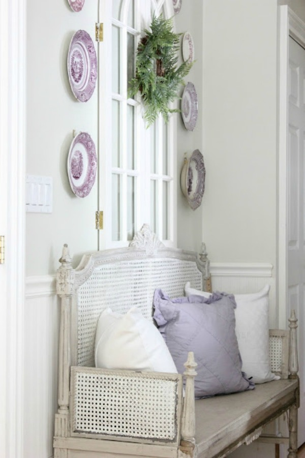 French country settee bench with purple transferware plates displayed on wall above - Maison Decor/Amy Chalmers. #frenchcountry #settee #interiordesign