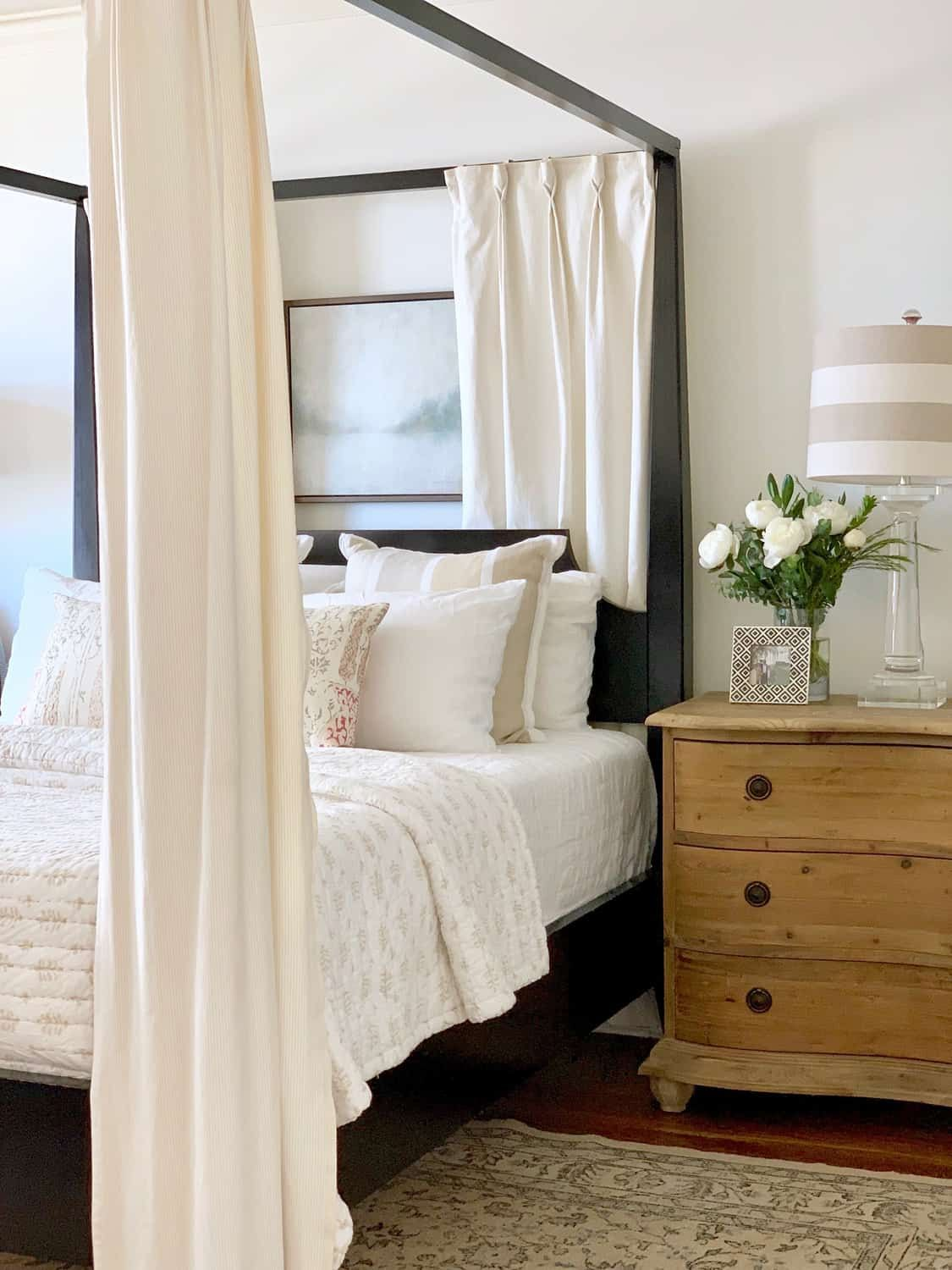 Serene bedroom decor with black and white and curtains on poster bed - Classic Casual Home. #bedroomdecor #blackbed #bedroomfurniture #classicbedroom #blackandwhite