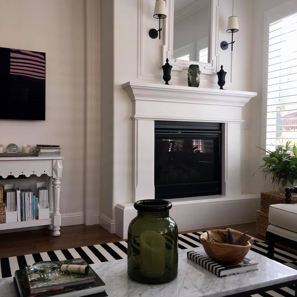 Classic living room with black and white stripe rug and beautiful white framed fireplace - Good Life of Design. #livingrooms #livingroomdecor #blackandwhite