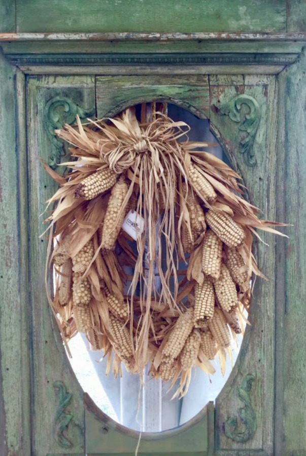 A charming dried corn cob wreath on a door in autumn by Marsha Smith - Cottonseed Trading Company. #falldecor #fallwreath #corncob #wreaths