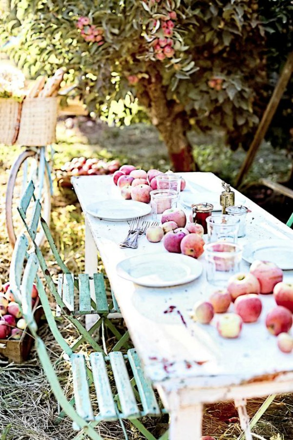 What a dreamy picture of French farmhouse fall bliss in this outdoor dining vignette with farm table and bistro chairs - Dreamy Whites Atelier. Serene French Farmhouse Fall Decor Photos ahead!  #frenchfarmhouse #fallinspiration #apples #harvest #farmtable