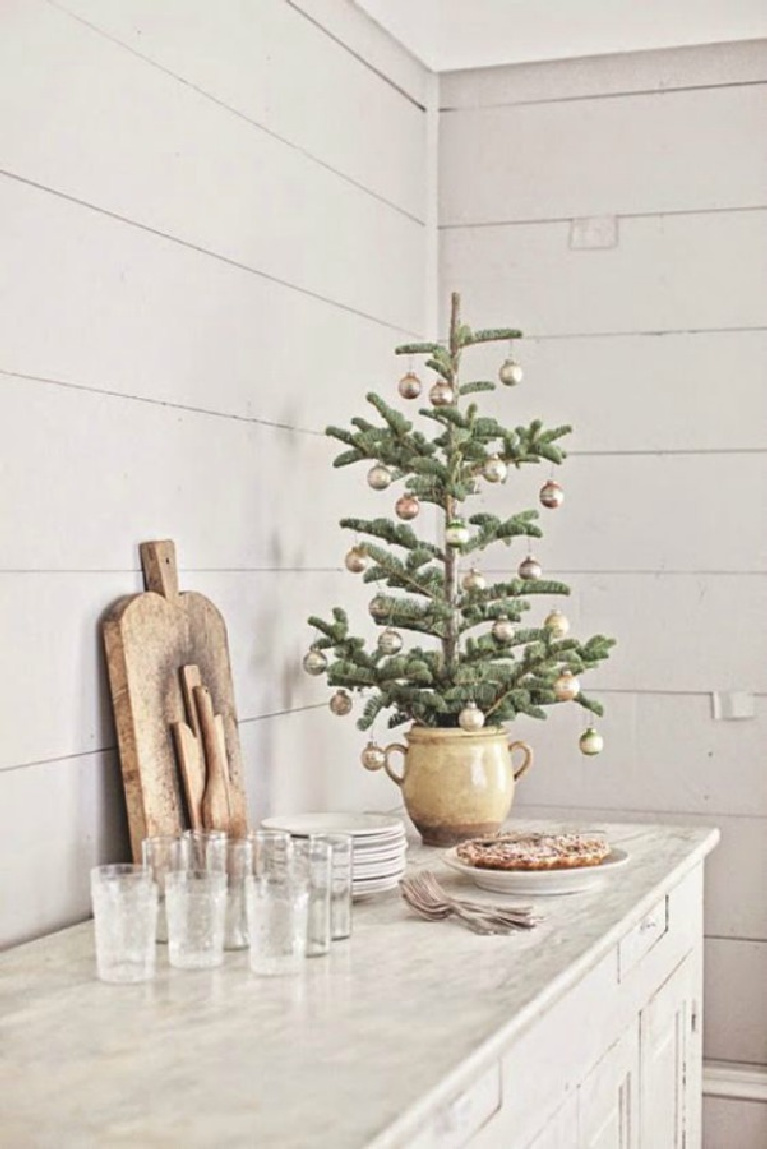 French farmhouse Christmas decor vignette on a buffet with whimsical fresh tree, vintage cutting boards, and white shiplap - Dreamywhites.