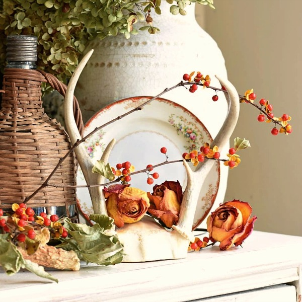 A French Country fall vignette with bitterroot, urns, and French vintner's basket pulls on the heartstrings and feels warm and charming - Follow the Yellow Brick Home. #frenchcountry #interiordesign #stilllife #falldecor #bitterroot #vintnerbasket