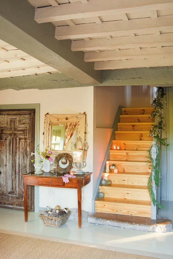 Rustic wood stair in a romantic french country cottage decorated with white and pink in Spain is decorated for Christmas with soft and quiet decor. #holidaydecor #christmasdecor #frenchcountry #decorating #cottagestyle #whitechristmas