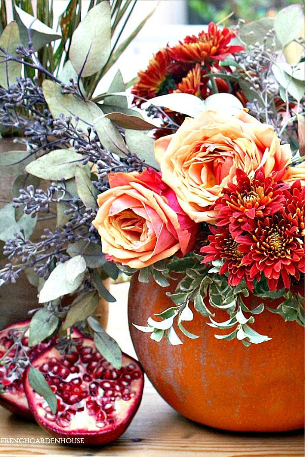 Breathtaking and vividly colorful fall blooms in a pumpkin vase for autumn splendor by FrenchGardenHouse. #pumpkin #centerpiece #fallfloral #autumntable