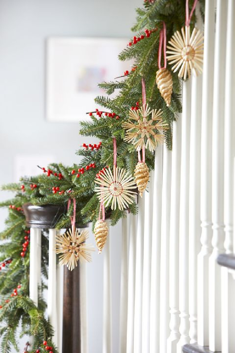 Charming Scandinavian Christmas straw ornaments and fresh garland on white staircase in a cottage style home.