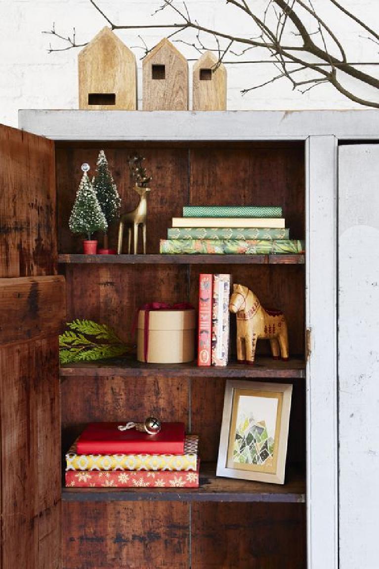 Farmhouse Christmas decorated shelves with bottle brush trees and Swedish dala horses.