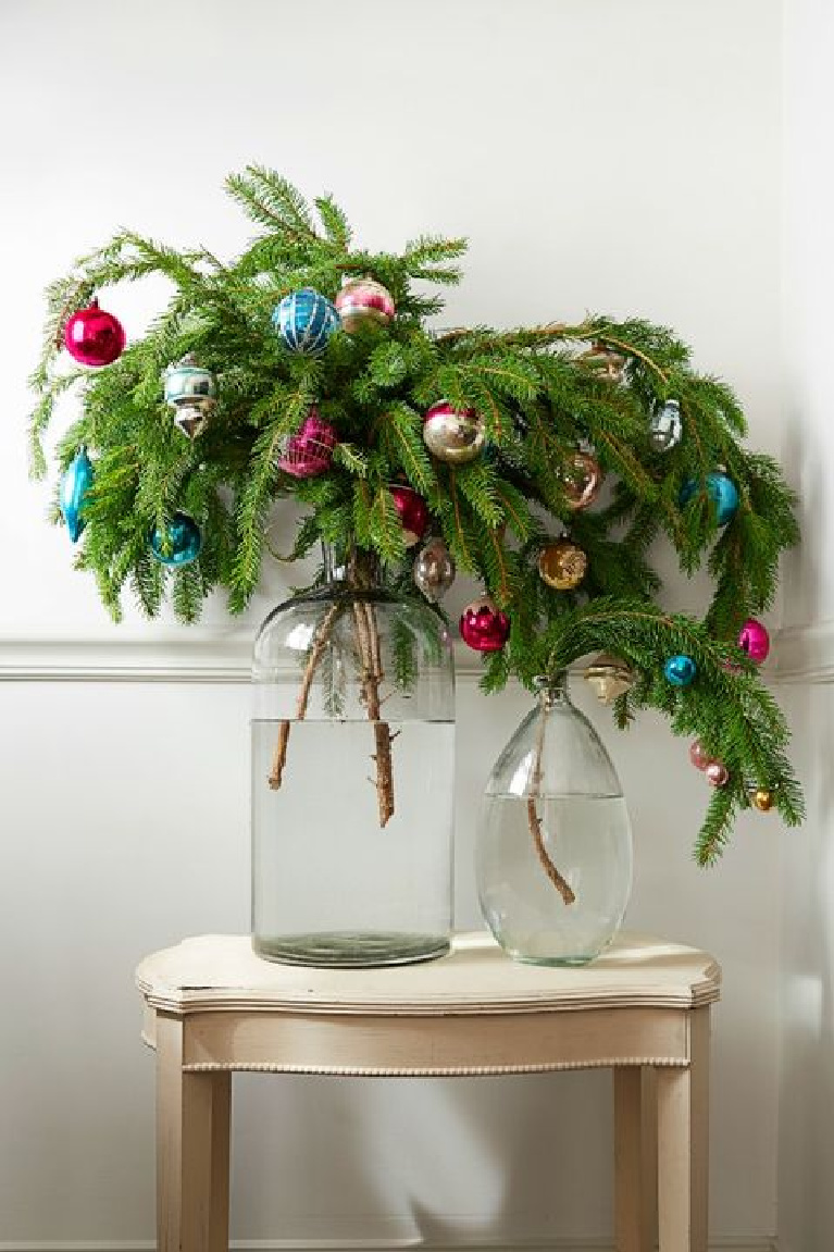 Charming and whimsical farmhouse Christmas decor with droopy evergreen branches decorated with colorful bulbs in simple white bottle vases.
