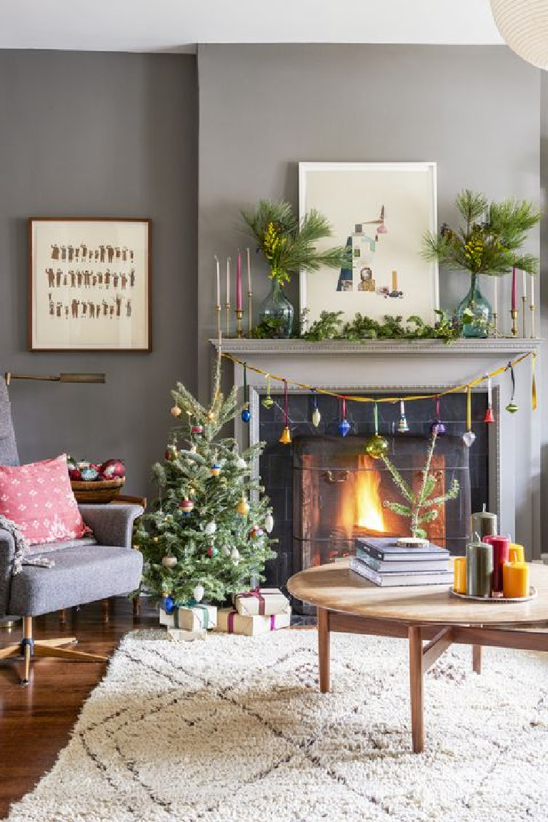 Casual living room with cheerful boho whimsical holiday decor and mini Christmas tree.