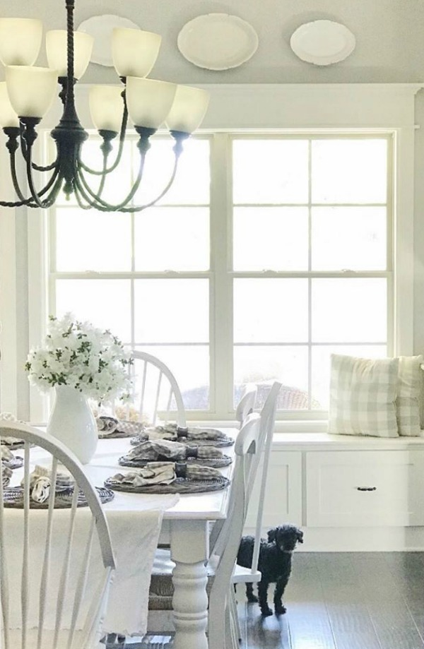 A window seat in the kitchen may be the best seat in the house...especially when the white cottage kitchen is this charming - Maven Haven. #whitekitchen #cottagestyle #windowseat #interiordesign #ironstone
