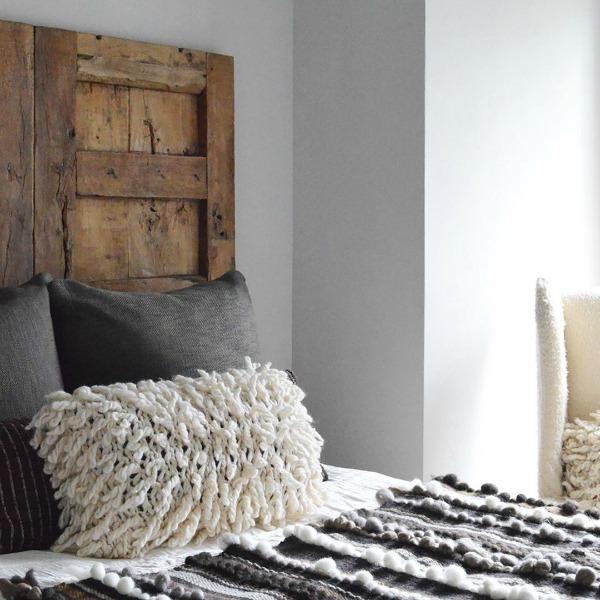 Rustic yet refined bedroom design with vintage wood door in lieu of headboard. Design by Michael del Piero. #bedroomdesign #rusticdesign #timelessdesign #interiordesign #headboard