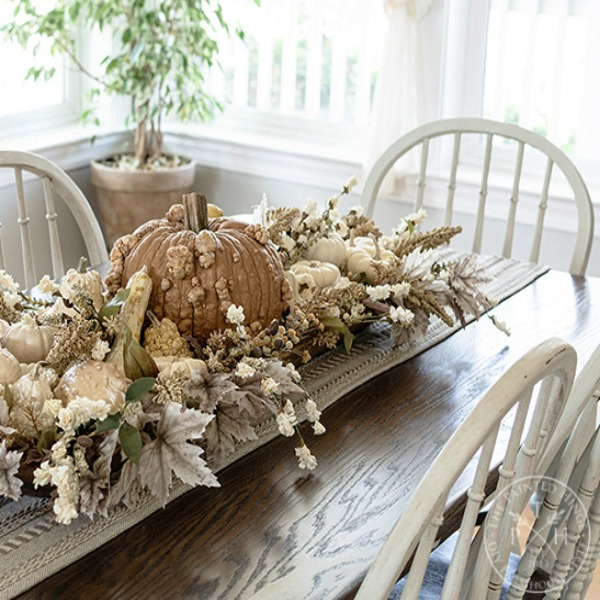 Soothing, serene, and calm colors in this rustic elegant farmhouse style pumpkin centerpiece by The Painted Hinge. Serene French Farmhouse Fall Decor Photos ahead! #fallcenterpiece #frenchcountry #frenchfarmhouse #tablescape #autumndecor