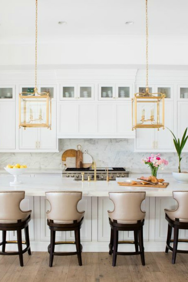 Airy and bright white kitchen with brass lantern pendants over island in a modern French home in Queen Creek, AZ. #modernfrench #kitchendesign #brasspendant